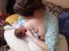 Dojčenie dvojčiat, mamička pomáha jednému z nich vypiť viac mlieka stláčaním prsníka