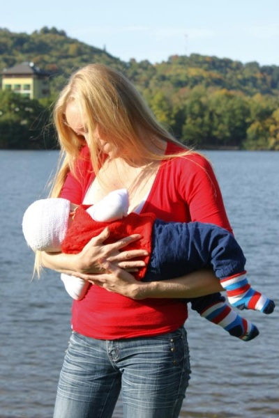 Na tomto obrázku sa maminka s dieťatkom dojčia vonku pri jazere - zladení v každom zmysle