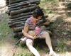 Maminka s jedenásť-mesačným synčekom sa dojčia v prírode na polienkach
